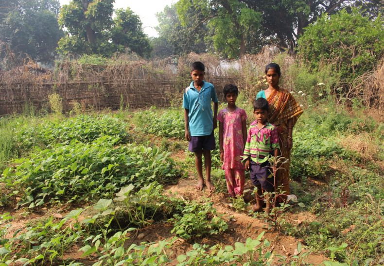 Anna with her children in her nutrition garden getting vegetables 9 months in a year